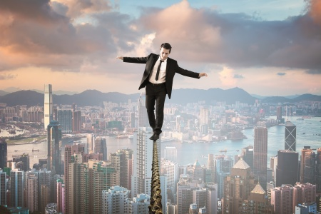 businessman in equilibrium on wire upon the city