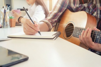 Cropped shot musician artist working on workplace with guitar on hand and holding a pencil writing on notebook paper,song writer concept.